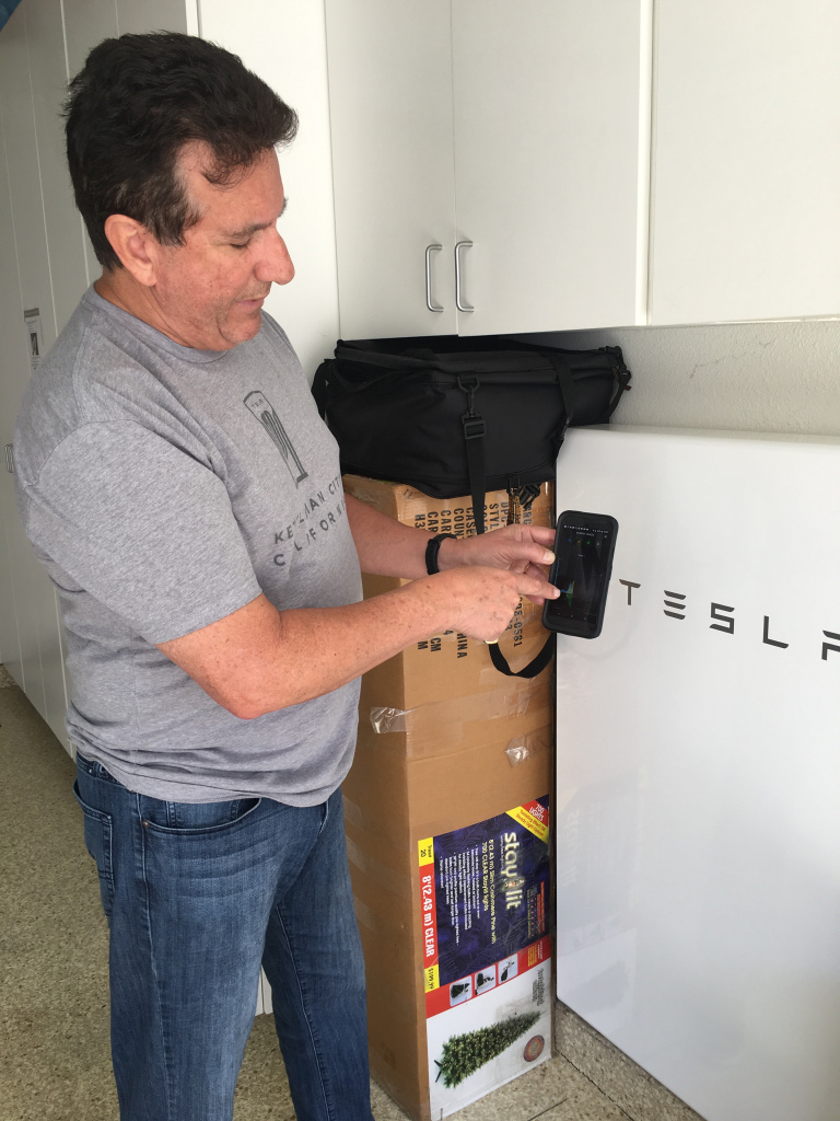 Kirk Nason shows how he tracks the electricity generated by his solar panels on his phone. Some of the power is stored in his Tesla PowerWall, a home battery system visible in the background.