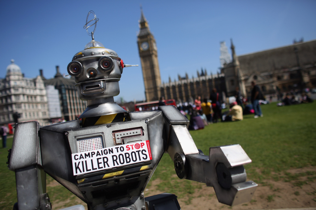 A robot distributes promotional literature calling for a ban on fully autonomous weapons in Parliament Square on April 23, 2013 in London, England. The 'Campaign to Stop Killer Robots' is calling for a pre-emptive ban on lethal robot weapons that could attack targets without human intervention.