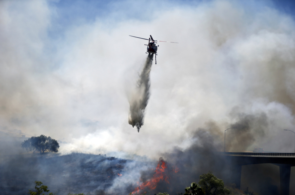 A helicopter attacks a wild fire burning  Tuesday, May 13, 2014, in San Diego. Wildfires destroyed a home and forced the evacuation of several others Tuesday in California as a high-pressure system brought unseasonable heat and gusty winds to a parched state that should be in the middle of its rainy season. (AP Photo)