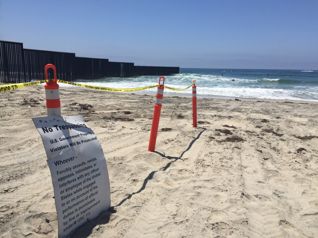 """A """"No Trespassing"""" sign warns beach-goers at Border Field State Park in San Diego from wandering too close to the fence separating the U.S. and Mexico. August 12th, 2017."""