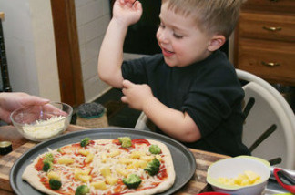 Owen Levine, 3, helps make a broccoli and pineapple pizza for Meatless Monday.