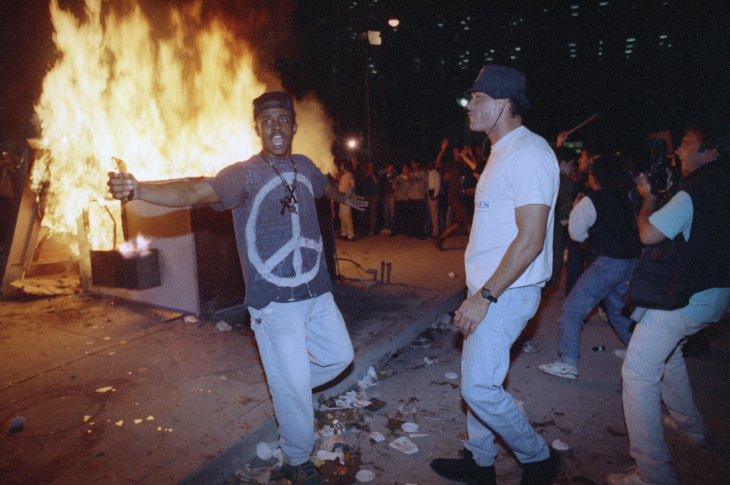 A rioter breaks a glass door of the Criminal Courts building in downtown Los Angeles on April 29, 1992.
