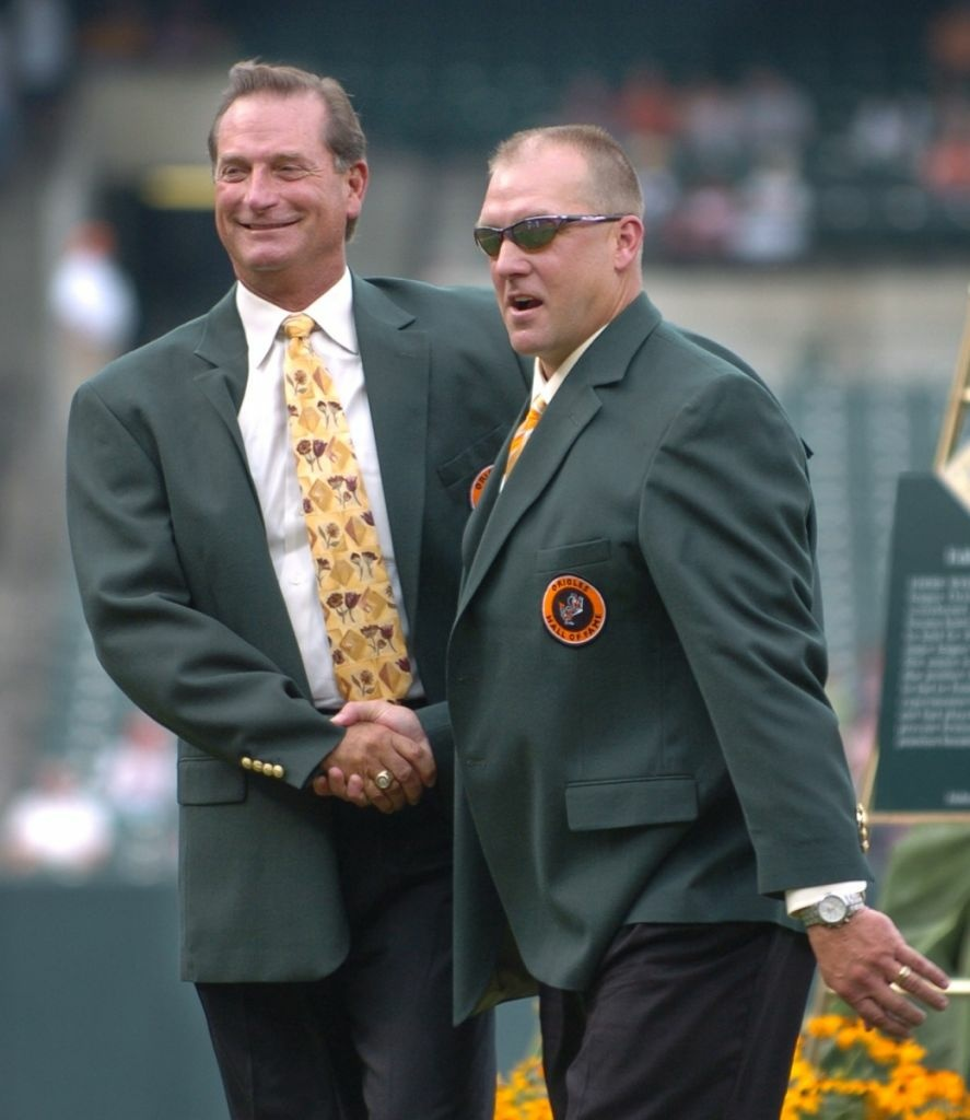 Former Baltimore Orioles' Doug DeCinces, left, and Chris Hoiles shake hands after being inducted into the Orioles Hall of Fame during a ceremony before the Orioles' baseball game against the Tampa Bay Devil Rays on Saturday, Aug. 26, 2006, in Baltimore.