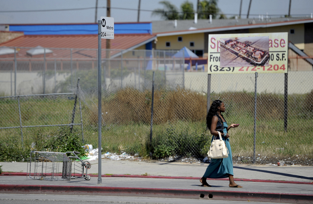 In this Tuesday April 17,2012 photo a woman walks past an empty lot on Vermont Ave. between 85th St. and Manchester Ave. in South Central Los Angeles. Several large stores once occupied the lot that was looted and set afire during the riots of 1992.