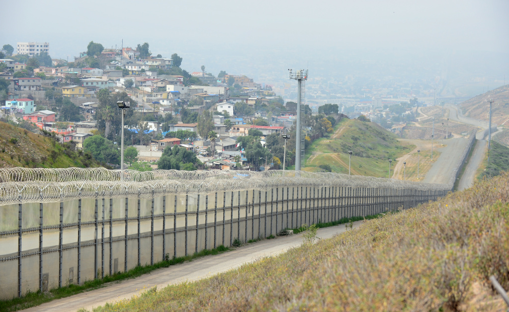 A fence runs along the US-Mexico border between the Otay Mesa and San Ysidro ports of entry in and near San Diego, California, across from Tijuana, Mexico.