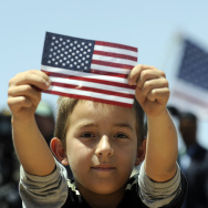 A boys shows a US flag as President Bara