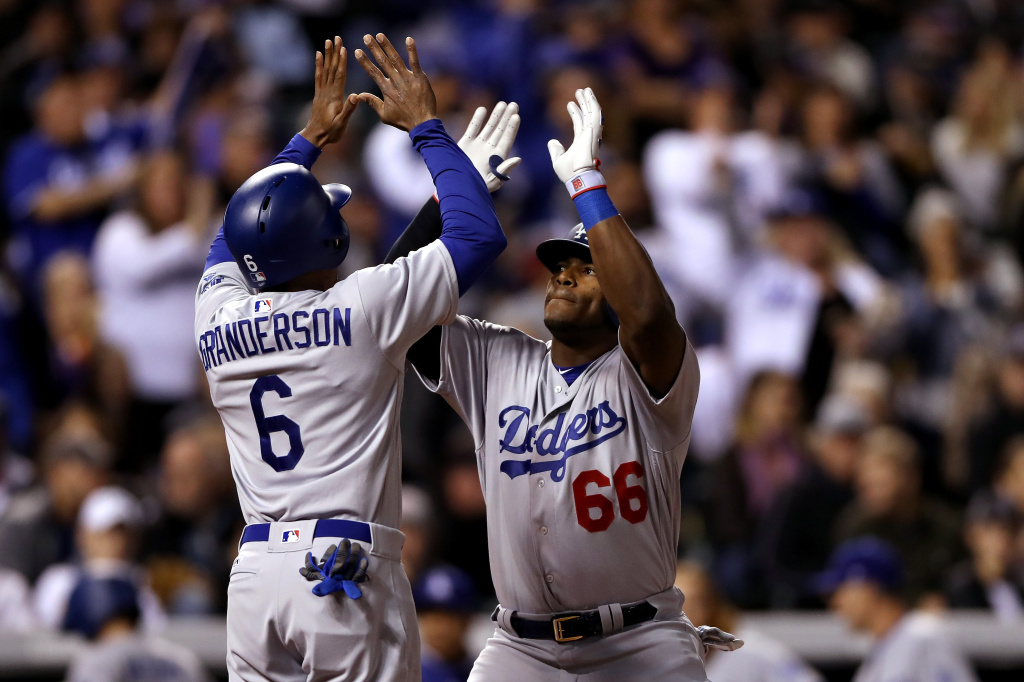 Yasiel Puig #66 of the Los Angeles Dodgers is congratulated by Curtis Granderson #6 after hitting a 2 RBI home run in the fifth inning against the Coloarado Rockies at Coors Field on September 30, 2017 in Denver, Colorado.