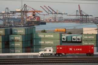 A truck passes shipping containers at China Shipping at the Ports of Long Beach and Los Angeles, the busiest port complex in the U.S. in Sept. 2008.