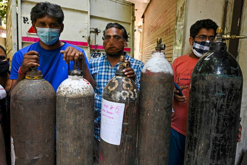 People wait in a line to refill oxygen cylinders for Covid-19 coronavirus patients at a refilling centre in New Delhi on May 5, 2021.