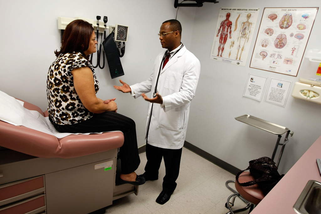Emlyn Louis, MD speaks with Julia Herrera as he examines her at the Broward Community & Family Health Center.