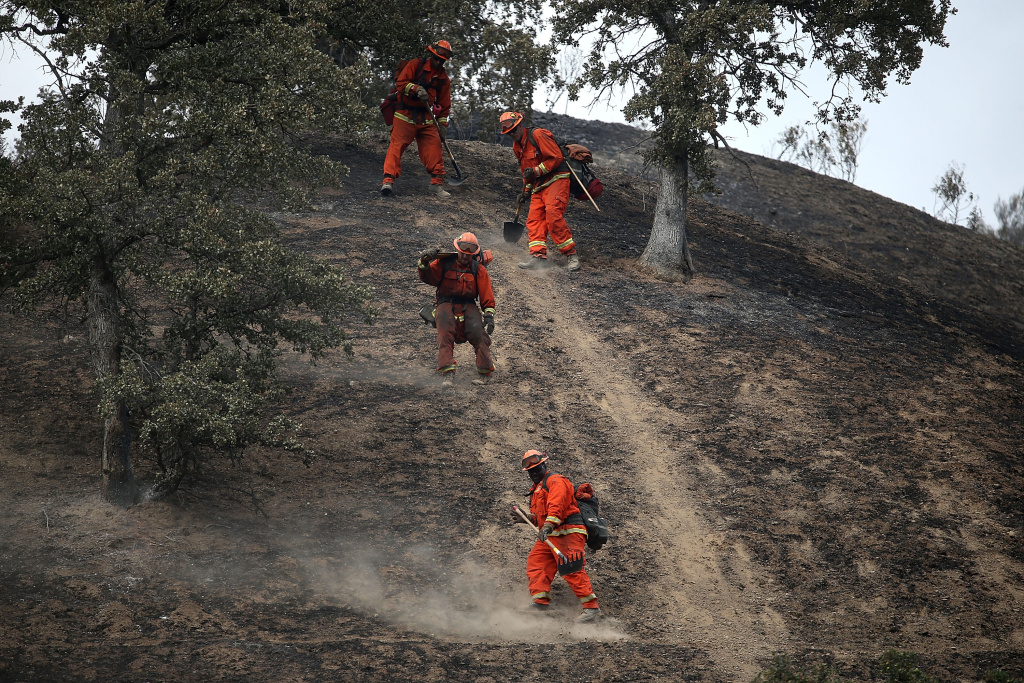 Firefighters hike down a hill as they mop up hot spots from the Rocky on August 4, 2015 near Clearlake, California.