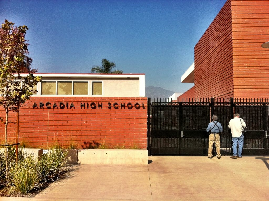 File: Two men stand outside of the Arcadia High School during the lockdown that began shortly before noon Tuesday, Nov. 1, 2011. Last week, schools in the San Gabriel Valley east of Los Angeles including Arcadia High School were shut down after hoax calls reporting campus gunmen.