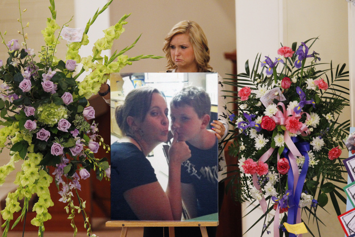 Hannah Anderson positions a photo of her mother, Christina Anderson, and brother, Ethan Anderson on an easel at the memorial service in Guardian Angels Catholic Church August 24, 2013 in Santee, California.