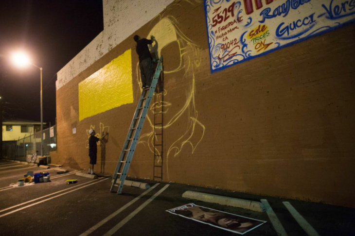 Graffiti Artist Edward Mompeller works on a mural on the side of Michael Kosman's Triumph Optical shop in Highland Park.