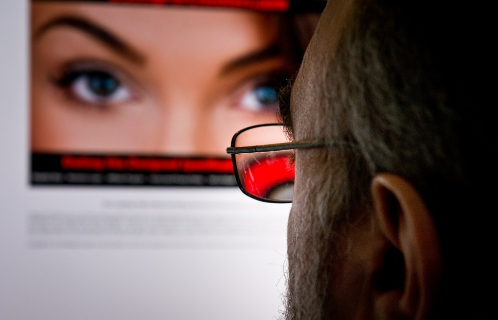 A man looks at a dating site on his computer in Washington,DC on February 10, 2014.