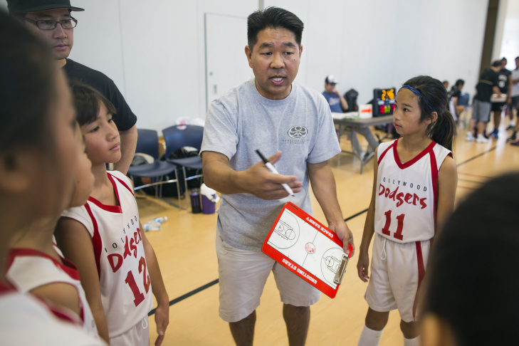 Fifth-grade players Emi Takara, left, Claudia Fan and Maiya Kuida-Osumi and the Venice Sparks take a timeout during the West Los Angeles Youth Club's Invitational Basketball Tournament at Rancho Dominguez Preparatory School in Long Beach on Saturday morning, April 16, 2016. Southern California is home to decades-old Japanese American basketball leagues, in which more than 10,000 players of all ages participate.