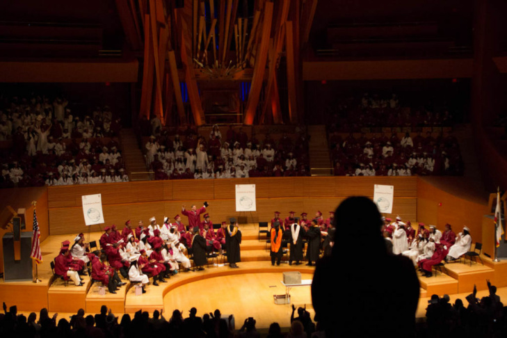 Students and attendees stand up and cheer as the diplomas are conferred. About 275 students were honored at the ceremony.