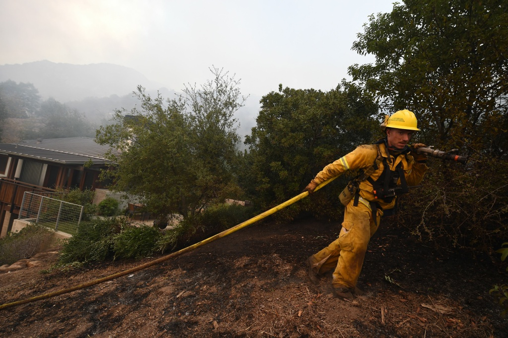 Napa City firefighter Nick Rizzo pulls a hose up a steep hill to protect structures from the Thomas Fire on December 16, 2017 in Montecito, California.