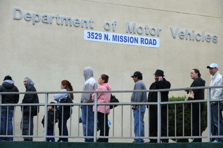 People wait in line outside of the State of California Department of Motor Vehicles (DMV) in Los Angeles, California.