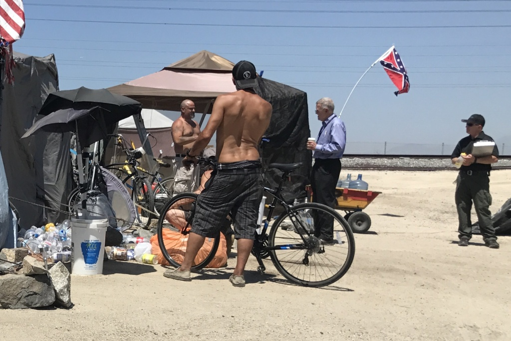Judge David O. Carter, lawyers and county officials stop to talk to a group of homeless men camped along the Santa Ana River in March 2017. Judge Carter is now presiding over a case that allowed for the riverbed homeless encampment to be cleared with the promise of finding appropriate shelter for the some 700 people still living there in February 2018.
