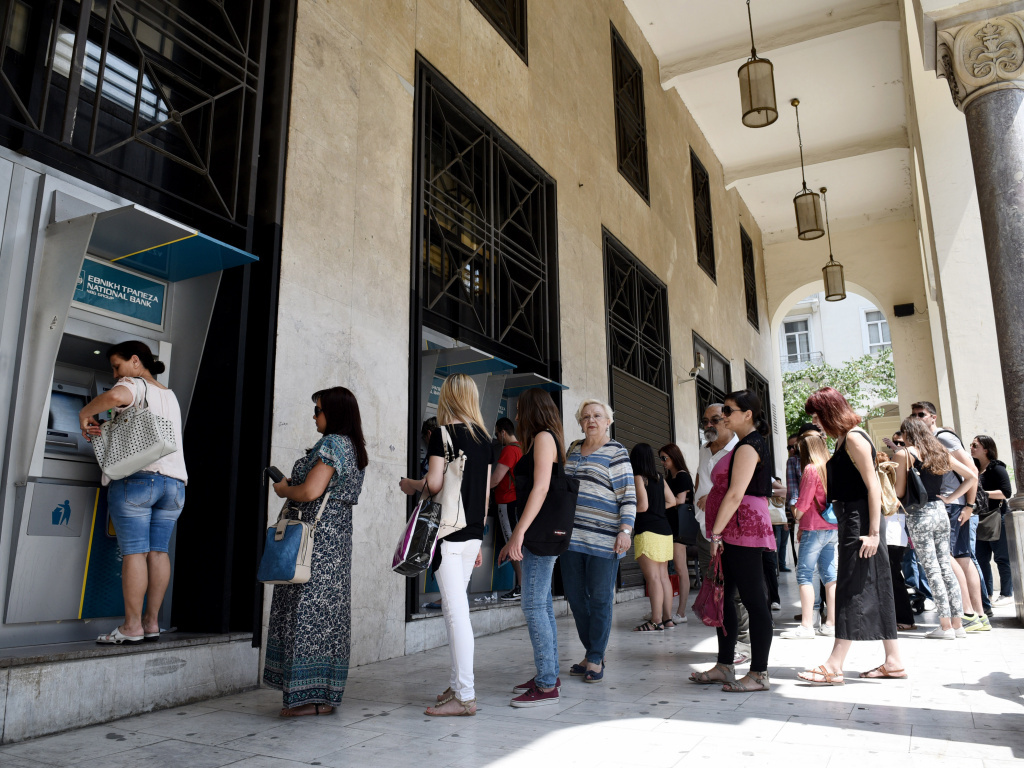 People stand in a line to use the ATMs of a bank in the northern Greek city of Thessaloniki on Saturday after the country's prime minister announced a snap referendum on an international bailout — pushing Athens toward a Tuesday deadline for a plan to prevent default on its IMF debt.