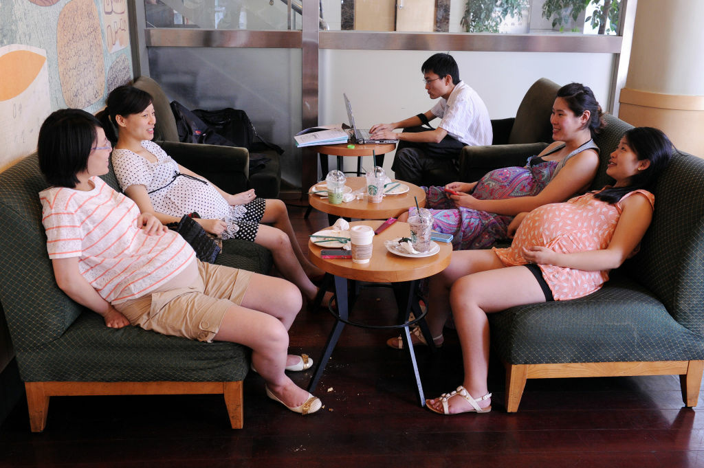 This file photo taken on July 30, 2011 shows four pregnant women relaxing in a coffee shop during a support group meeting at a shopping center in Shanghai.