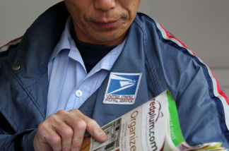 U.S. Postal Service letter carrier Raymond Hou sorts through mail as he delivers mail along his route March 2, 2010 in San Francisco, California.