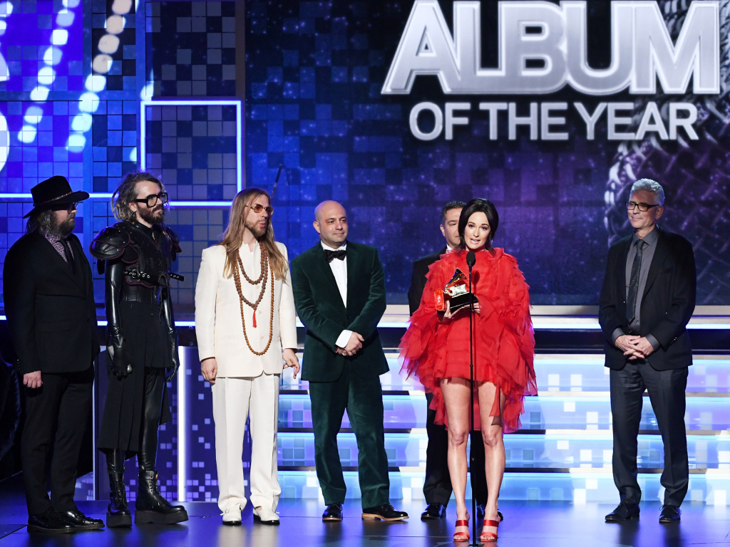 Kacey Musgraves (speaking at microphone) won the Grammy for Best Album of the Year for <em>Golden Hour</em>.