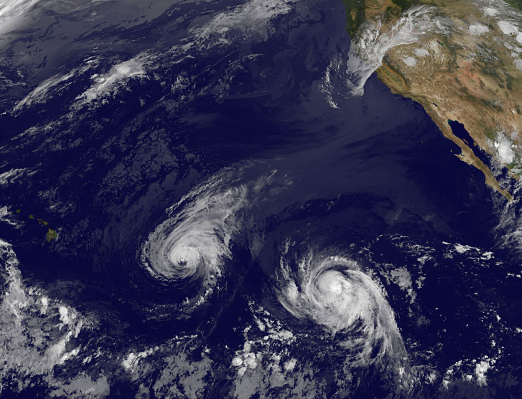 This image provided by NOAA taken Wednesday Aug. 6, 2014 shows Hurricane Iselle, center, and tropical storm Julio, right. Though it's not clear how damaging the storms could be, many in Hawaii aren't taking any chances as they wait for Hurricane Iselle to make landfall later this week and Tropical Storm Julio potentially hitting a few days later.
