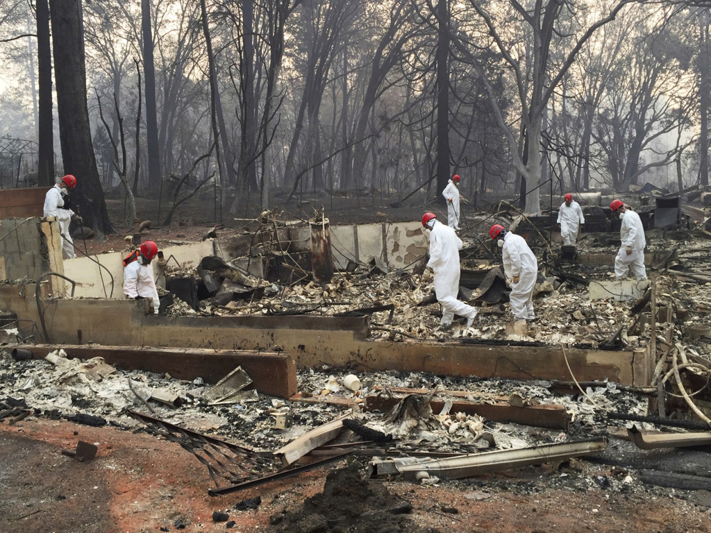 Volunteer rescue workers search for human remains in the rubble of homes burned in the Camp Fire in Paradise, Calif. State officials say the fire was caused by PG&E power lines.