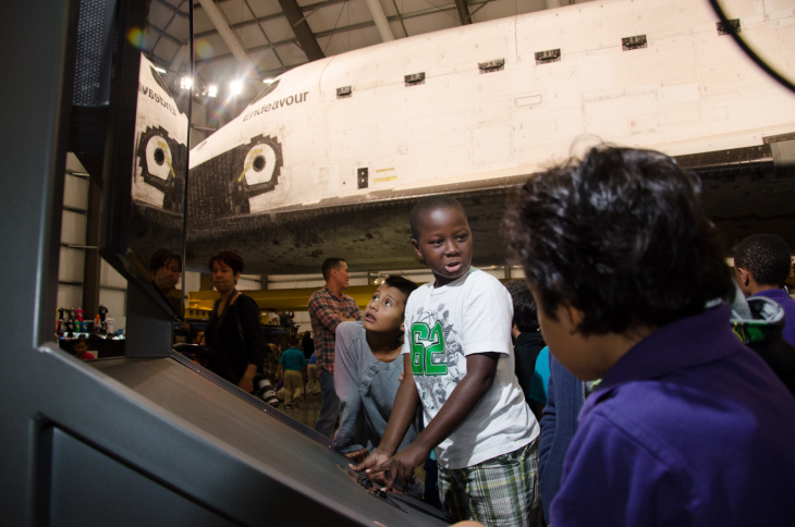 A group of children watch a display about the shuttle during the grand opening of the Space Shuttle Endeavour Exhibition at the California Science Center in Los Angeles, Calif., October 30, 2012. Children and adults got the chance to meet astronauts and learn about the shuttle.