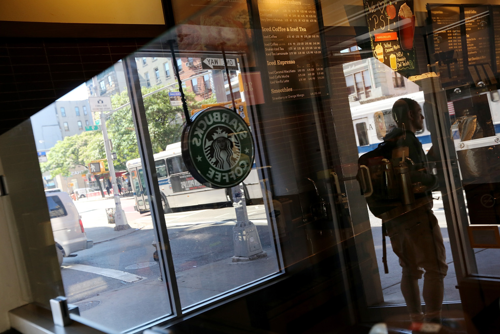 A man exits a Starbucks cafe in Manhattan on September 18, 2013 in New York City. Starbucks announced it will no longer welcome guns inside its cafes following the Washington Navy Yard shootings which left 13 dead.