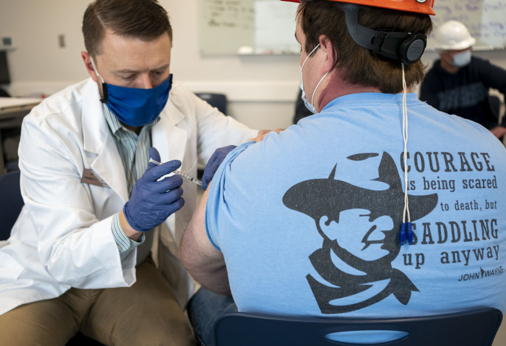 A pharmacist administers a dose of the COVID-19 vaccine to a worker at a processing plant in Arkansas City, Kan., on Friday, March 5, 2021. Researchers are concerned that vaccination rates in some rural communities may not keep up with urban rates.