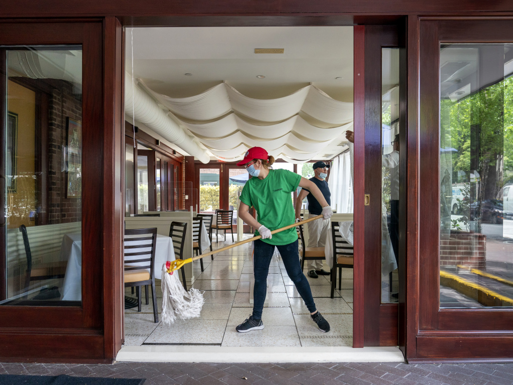A cafe employee in Washington, D.C., cleans in preparation for reopening.