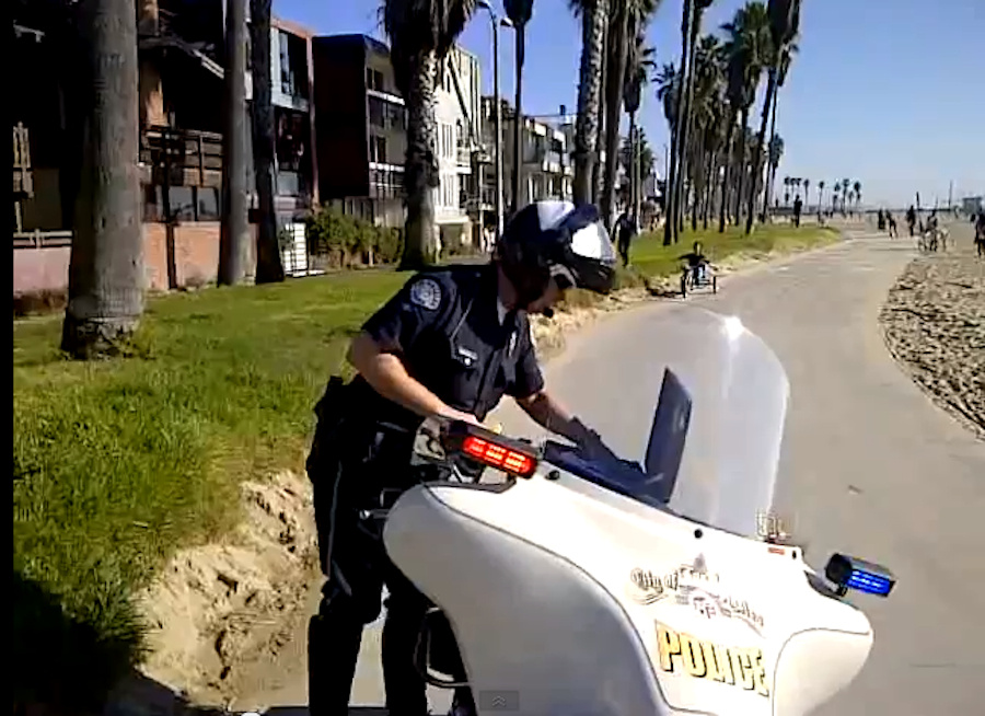 An unidentified LAPD officer is filmed while writing a ticket on the Venice Boardwalk. The image is taken from a video of the incident published on the Internet that has gotten more than 300,000 views.