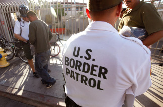 An U.S. Border Patrol bike patrol agent in Nogales, Arizona assists Mexican nationals being returned to Mexico after they were apprehended entering the United States illegally, June 2, 2010. As federal sequester budget cuts loom, border security and the legal immigration system could take a financial hit.