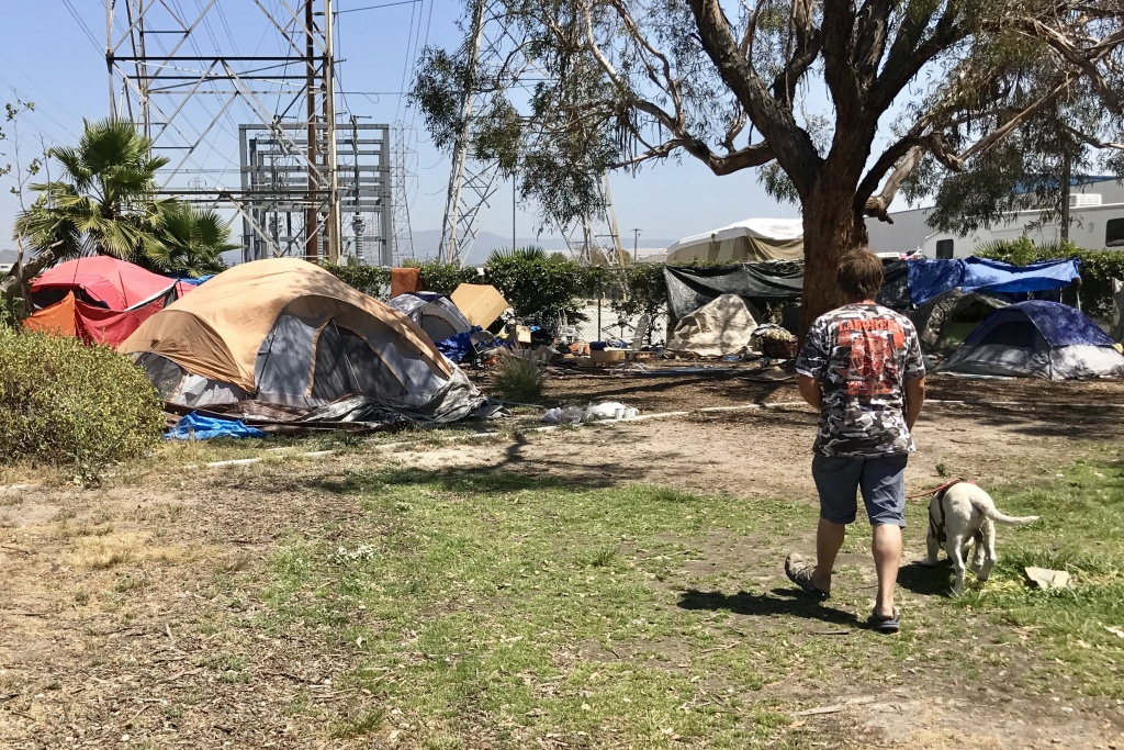 A homeless man walks back to his tent along the Santa Ana River. Advocates for the homeless want to install port-a-potties on nearby land owned by the city of Anaheim.