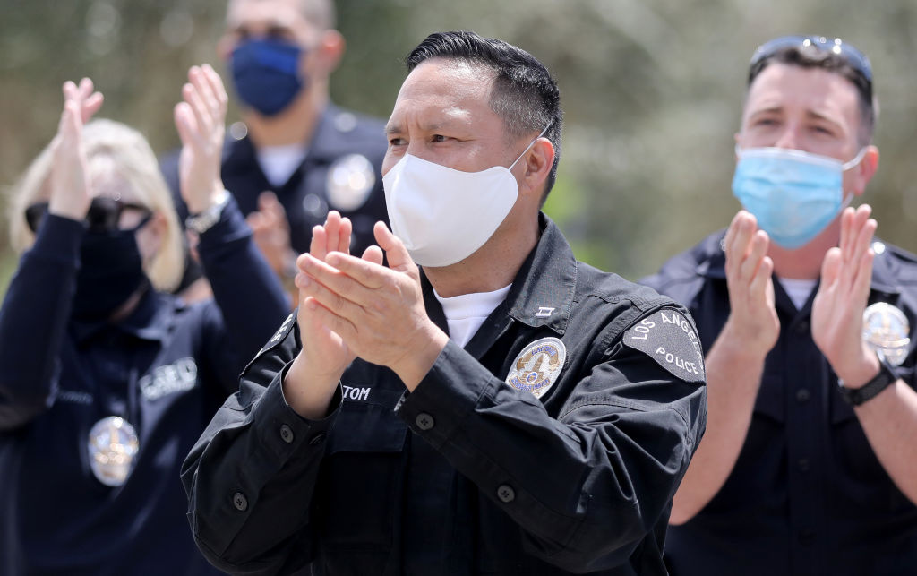 Los Angeles Police Department officers salute healthcare workers after fellow LAPD Detective Michael Chang was released from Providence St. John's Health Center following a long battle with the novel coronavirus on April 17, 2020 in Santa Monica, California.
