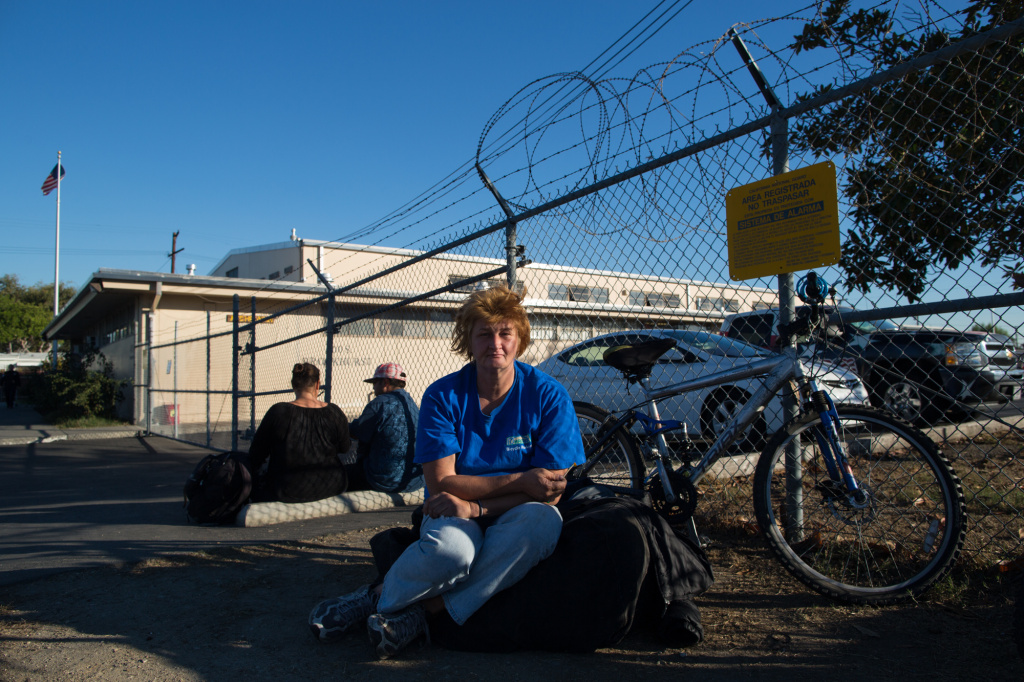 In this file photo, Kristen Konig sits in front of the Fullerton Armory, which offers housing for the homeless population in Orange County during the winter months. The shelter closes on April 15.