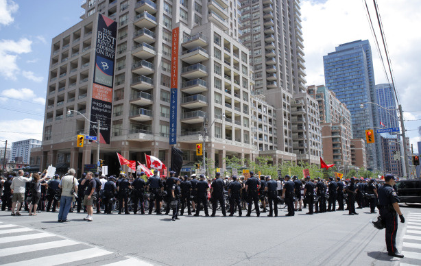 Canadian police forces watch over marchers taking part in the Indigenous Peoples assembly and march through the streets of Toronto two days prior to the opening of the G20 Summit on June 24, 2010 in Toronto, Canada.
