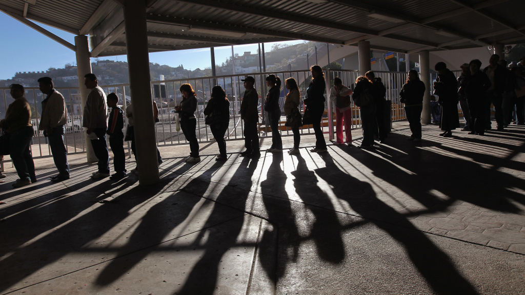 Hundreds of people wait to pass from Mexico into the United States at the border crossing in Nogales, Ariz., in 2010.