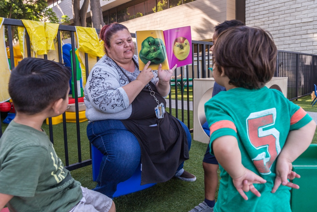 Rosa Lopez reads a book to kids at the Mexican American Opportunity Fund child care center in Norwalk. She's been in the child care field for 24 years and makes under $15/hr.