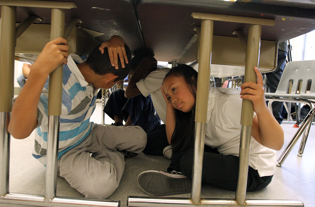 Third grade students at William L. Cobb Elementary School take cover under desks as they participate in the