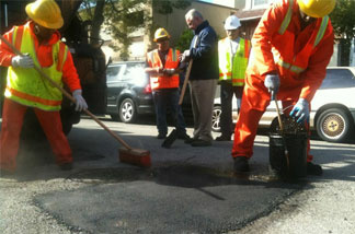 Los Angeles street services crew members Joyce Robinson and Ralph Jackson repair a pothole on Reno Street