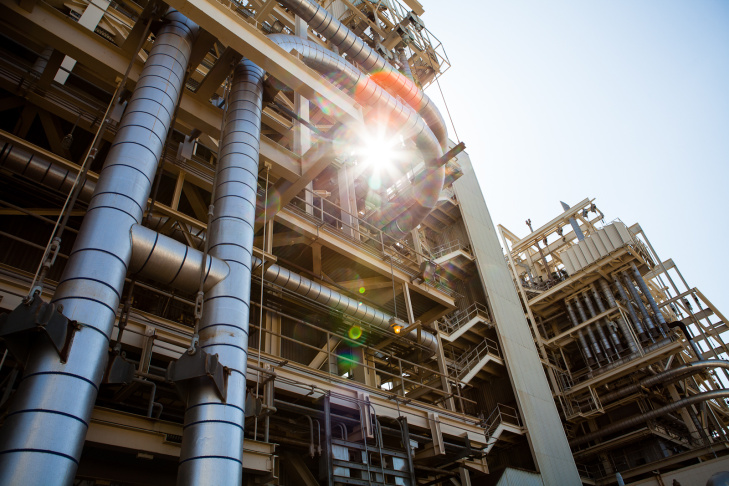 The sun shines through a maze of pipes at the AES Power Plant in Huntington Beach.