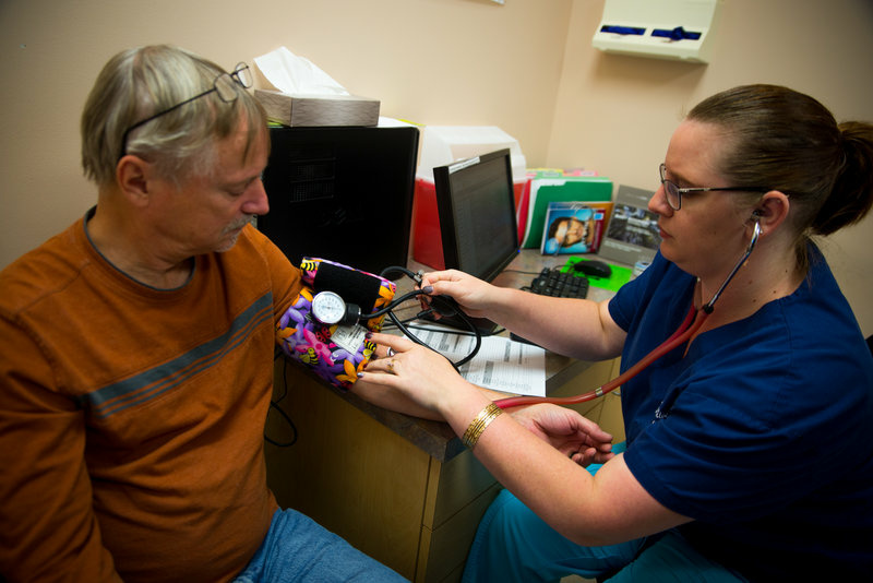 Emily Blair, a medical assistant at the Colon, Stomach and Liver Center in Lansdowne, Va., takes a blood pressure reading for Robert Koenen. New guidelines say that patients should have their arm resting on a surface while taking a reading and both feet should be placed flat on the ground.