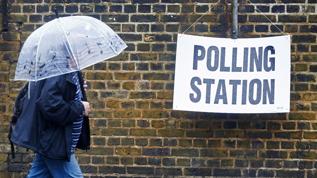 A man shelters from the rain as he walks toward a polling station in London.