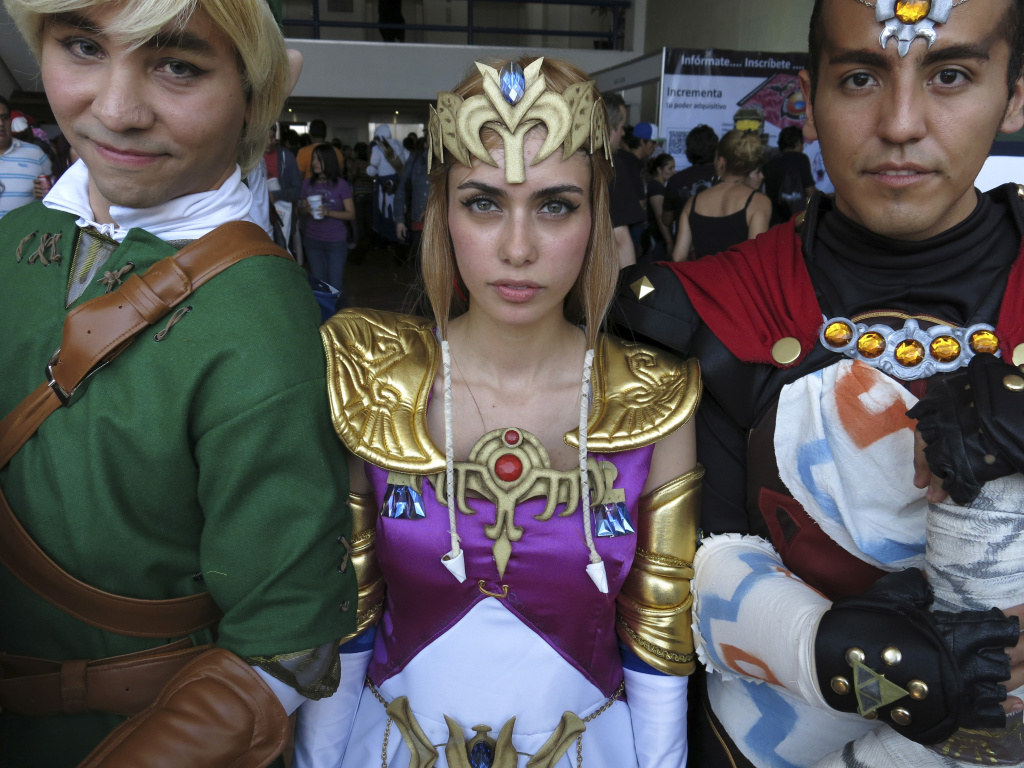 "File: In this July 27, 2013 photo, psychologist Andrea García, 26, dressed as Princess Zelda from Nintendo's popular video game saga ""The Legend of Zelda,"" poses for a photo flanked by Ángel Flores, 25, right, dressed as the action-adventure game's evil sorcerer Ganon or Ganondorf, and Ricardo Villanueva, 28, left, dressed as the hero and main character Link, as they arrive at La Mole Comic-Con Internacional in Mexico City."
