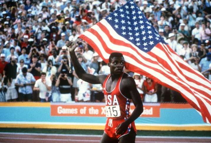 Carl Lewis holds the American flag after winning the 100m Men's final in 9:99, at the Los Angeles Olympic games, August 4, 1984. Four years later, at the Seoul 1988 olympic games, Lewis also took gold in the same category.