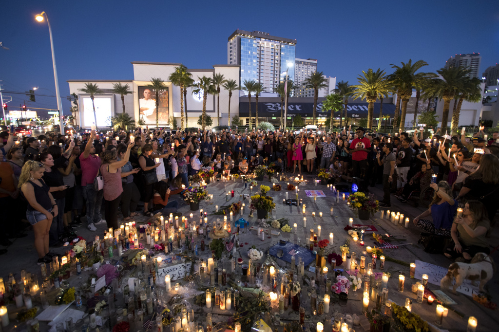 Mourners hold their candles in the air during a moment of silence at a vigil to mark one week since the mass shooting at the Route 91 Harvest country music festival on Oct. 8, 2017 in Las Vegas.